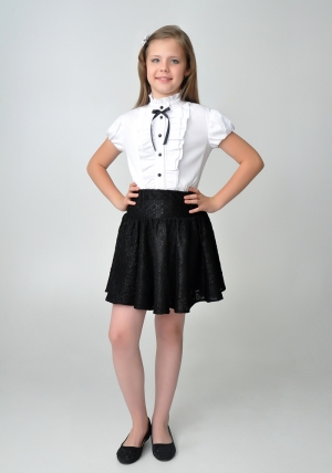 Детская блуза белого цвета с воротником стойкой и коротким рукавом.Нарядная блузка идеальный наряд для девочек школьного возраста. Школьная блузка, украшена спереди рюшами, а также черным бантиком и черными пуговицами. Оригинальный крой и цвет, позволяет носить как в школу, так и в повседневной жизни.
