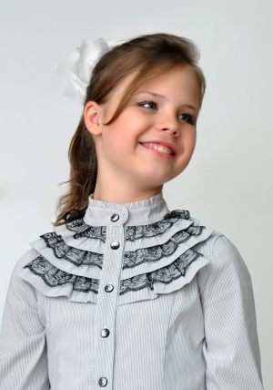 Школьная одежда для девочек! Нарядная блузка для девочки бело-серого цвета с длинным рукавом и воротником стойкой с рюшами черного кружева. Нарядная блузка - спереди украшена рюшами с черным кружевом. Очень красивая и нежная блузка, можно носить со школьным костюмом, юбкой или брюками. Также данную блузку можно носить на праздник или в повседневной жизни. Ткань эластичная, хорошо тянется.