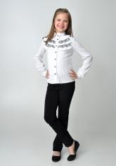 Детская блузка белого цвета с длинным рукавом и воротником стойкой с рюшами черного кружева.