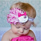 Детская повязка с перьями бело-малинового цвета.