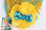Детская повязка с перьями желто-синего цвета.