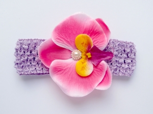Цветок орхидея ярко-розового цвета на повязке в сеточку.Повязка в сеточку хорошо тянется, цветок приклеен. Сердцевинка цветка украшена жемчужиной.