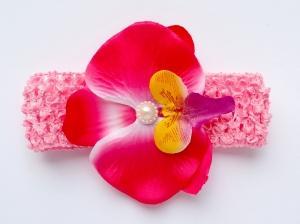 Цветок орхидея малинового цвета на повязке в сеточку.Повязка в сеточку хорошо тянется, цветок приклеен. Сердцевинка цветка украшена жемчужиной. Повязка идеальна для малышек и девочек.