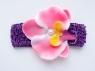 Цветок орхидея ярко-розового цвета на повязке в сеточку.
