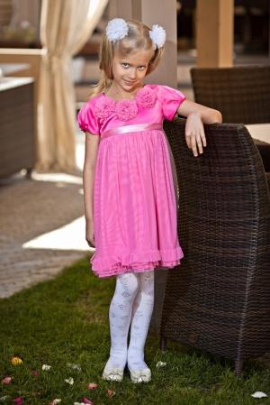 Нарядное платье-трапеция малинового цвета.Красивоеплатье для девочек с коротким рукавом с шифоновыми цветочками на груди и пышной юбкой. Вверх платья из атласа с атласным поясом, а юбка из шифона. Платье сзади застегивается на пуговку.