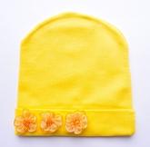 Желтая шапочка для малышек с оранжевыми цветочками.