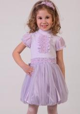 Нарядная юбка сиреневого цвета с розочками на поясе и большим бантом.